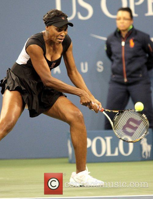 Venus Williams returns a serve during her match...