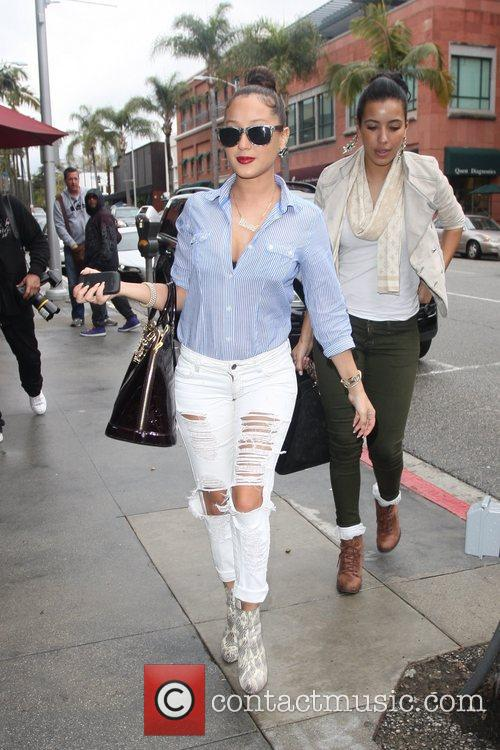 Adrienne Bailon wearing ripped white jeans as she...