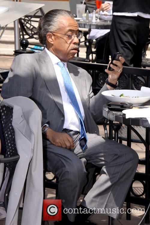 Al Sharpton checking his cell phone as he...