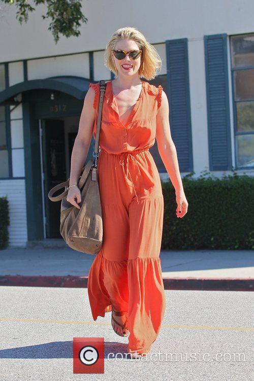 Ali Larter wearing a bright orange jumpsuit while...