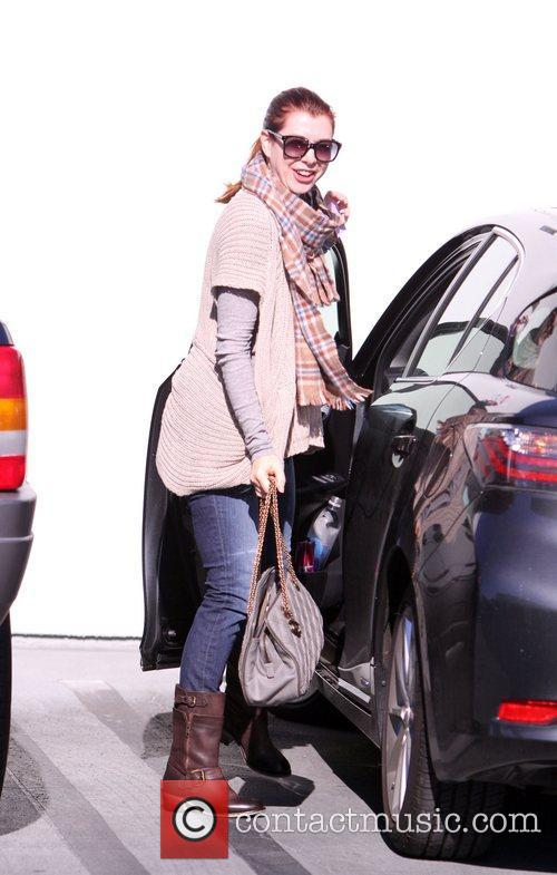 Alyson Hannigan wearing a plaid scarf and sunglasses...