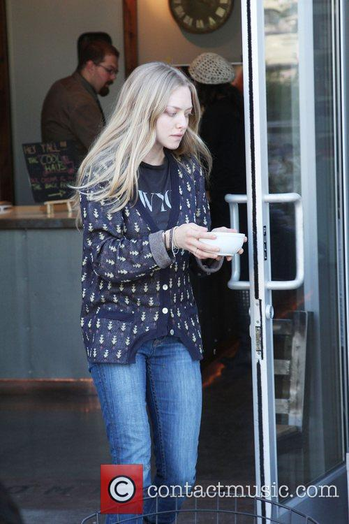 Amanda Seyfried carries a bowl of water to...