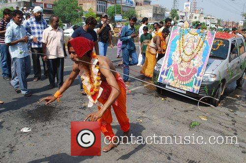 A Hindu devotee pulls a car with ropes,...