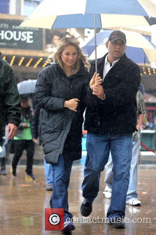 Tennis star Anna Kournikova shelters under an umbrella...