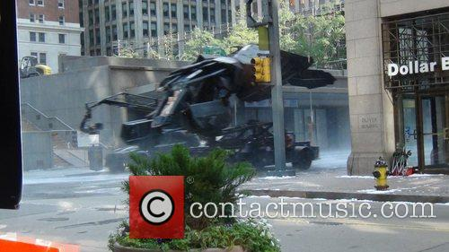 The Batplane is transported through a scene with...