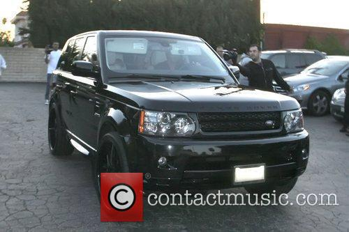 David and Victoria Beckham drive away from the...