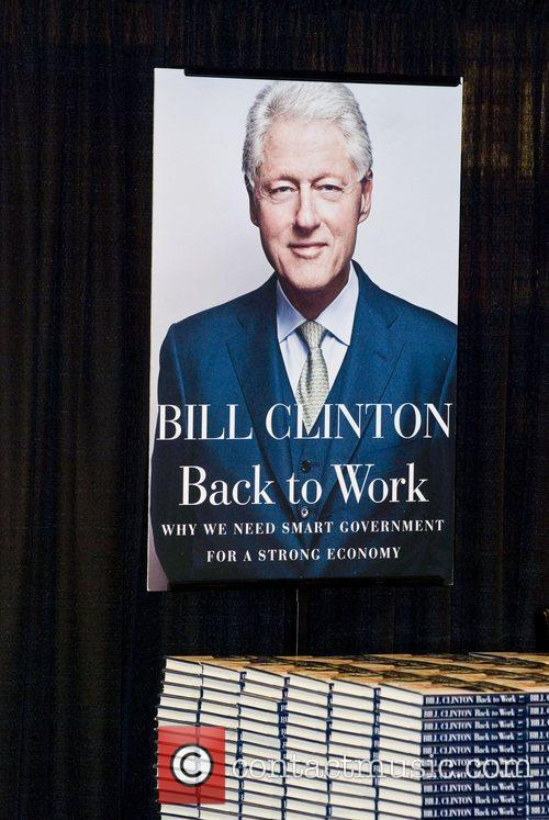 Former U.S. President Bill Clinton signs copies of...