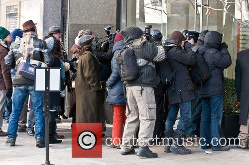 Extras playing paparazzi are seen on the set...