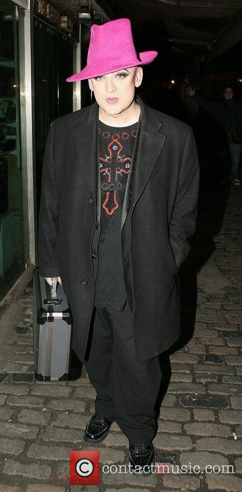 Boy George wearing his trademark hat in pink...