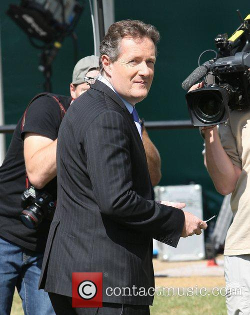 Piers Morgan filming outside Buckingham Palace during preparations...