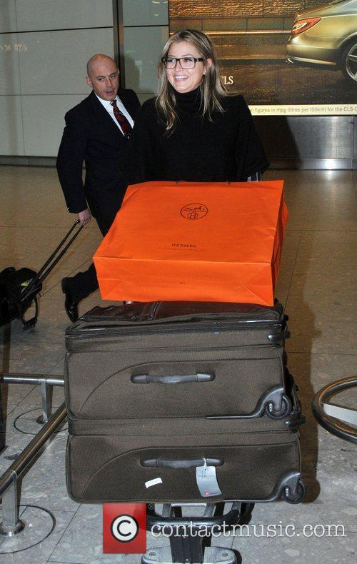 Holly Valance pushing a luggage trolley as she...