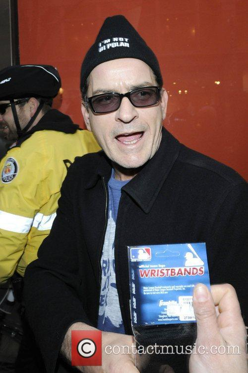Charlie Sheen accepts a package of wristbrands from...