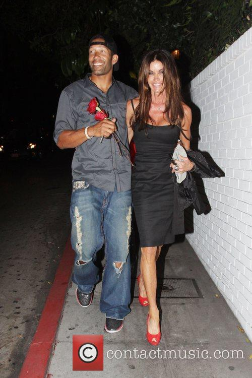 Janice Dickinson is escorted by a man with...