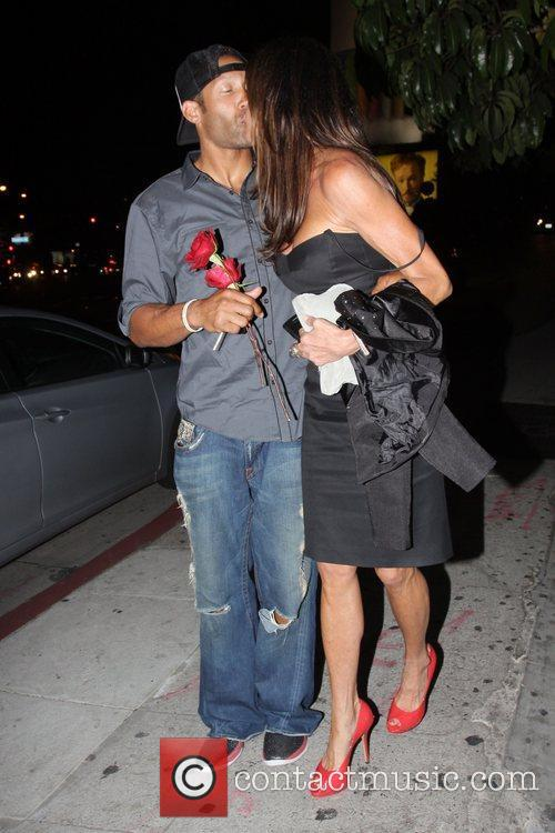 Janice Dickinson kisses a man with a rose...