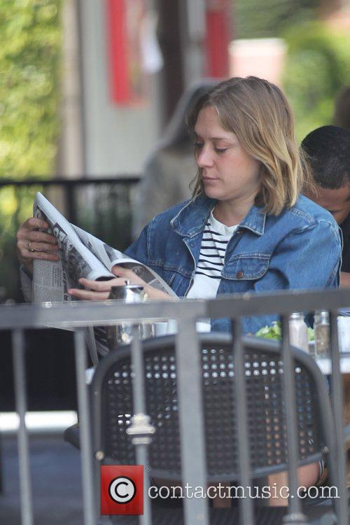 Chloe Sevigny reading a newspaper during lunch at...