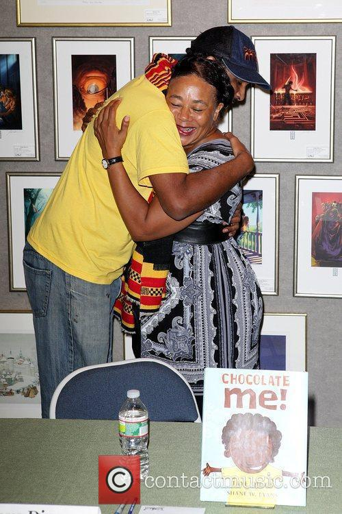 Illustrtor, Shane W. Evans hugs Marcia Berry Carter,...