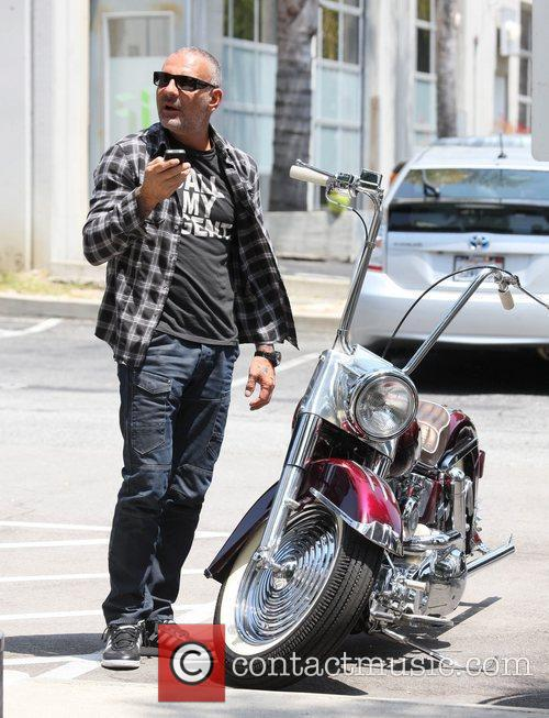 Christian Audigier  drives a vintage Harley Davidson...