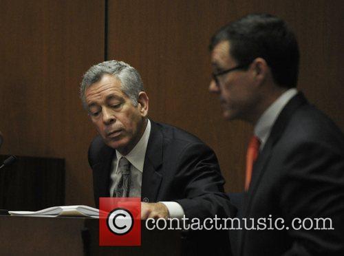 Defense attorney Ed Chernoff (R) approaches Dr. Robert...