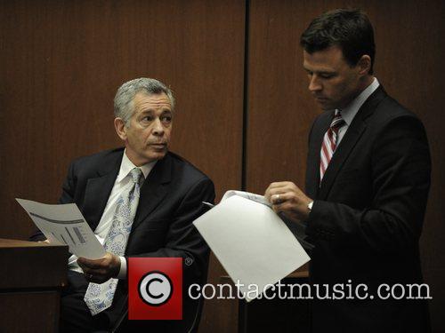 Shows documents to Dr. Robert Waldman (L), an...
