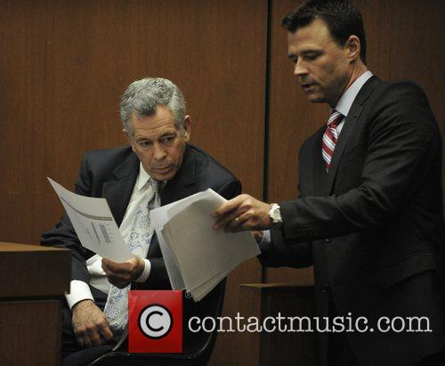 Deputy District Attorney David Wlagren shows documents to...