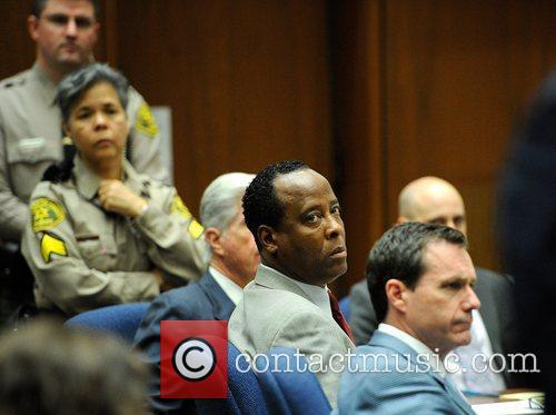Dr. Conrad Murray (2nd from R) looks toward...
