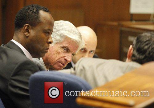 Dr. Conrad Murray (L) confers with his attorneys...