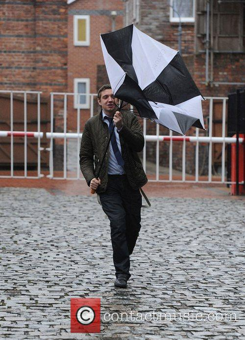 Struggles with his umbrella as he leaves Granada...