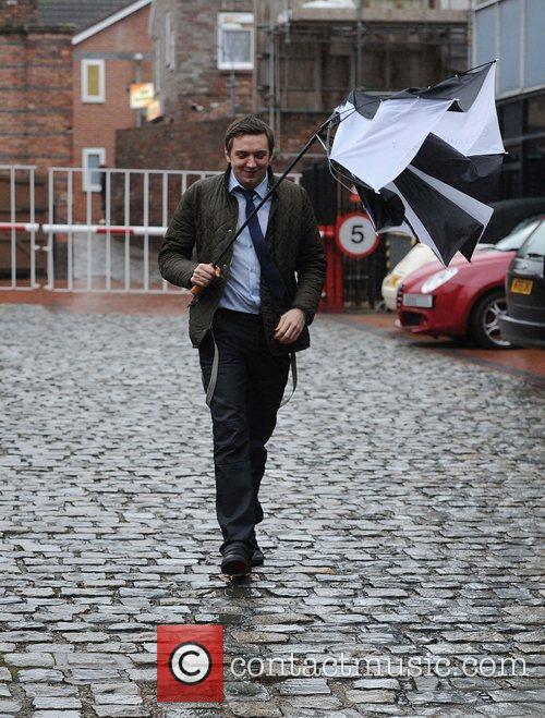 Craig Gazey struggles with his umbrella as he...