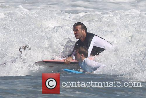 David Beckham  bodyboarding with his sons Brooklyn...