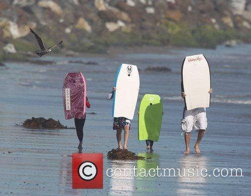 David Beckham  walking along Malibu Beach with...