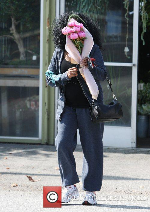 Diana Ross carries a bunch of flowers whilst...