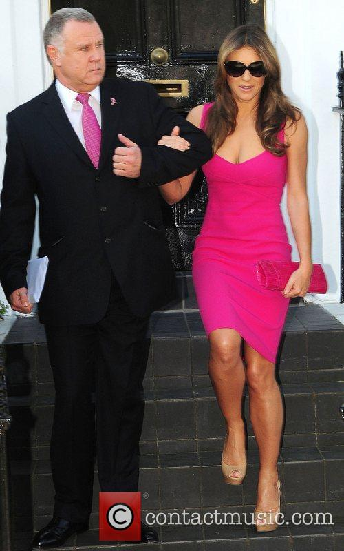 Elizabeth Hurley being help down her steps wearing...