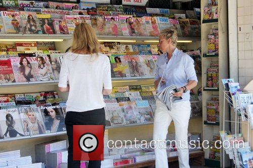 Ellen DeGeneres buys magazines at a newsstand with...