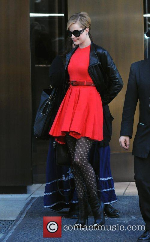 Leaving her hotel wearing a red dress, leather...