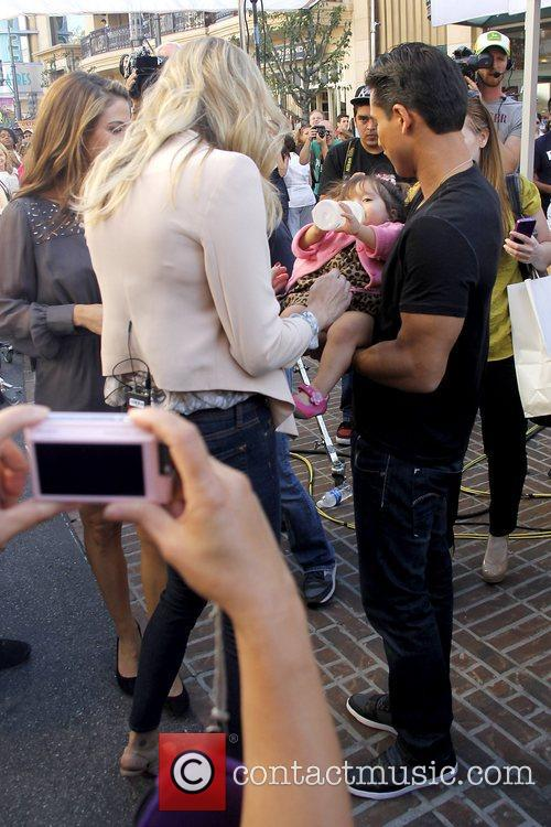 Mario Lopez, with Rebecca Romijn looking on with...