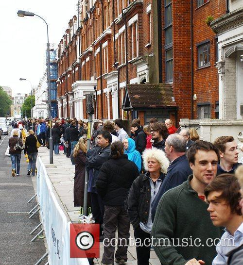 Tennis fans queue outside the Queens Club for...