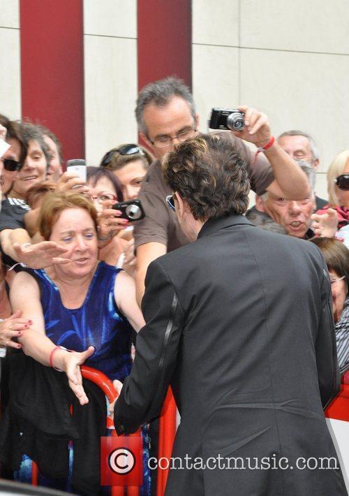 Johnny Hallyday shaking fan's hands outside Fun Radio...