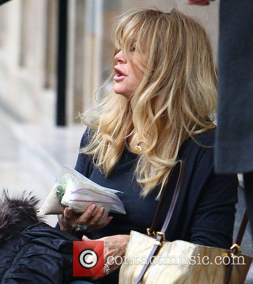 Goldie Hawn holds some plastic bags in her...
