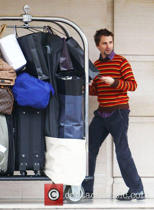 Matt Bellamy  pushes the luggage trolley outside...
