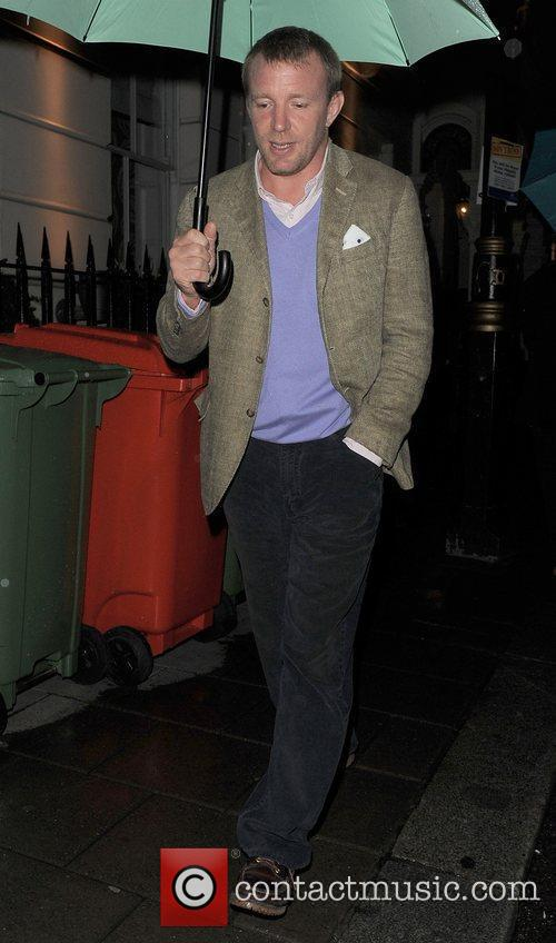 Guy Ritchie walking through Mayfair holding a large...