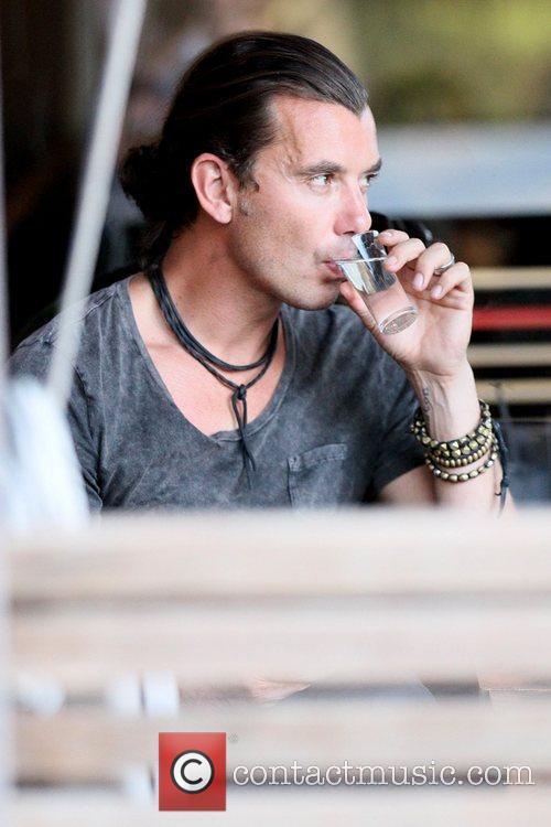 Gavin Rossdale drinking water as he eats with...