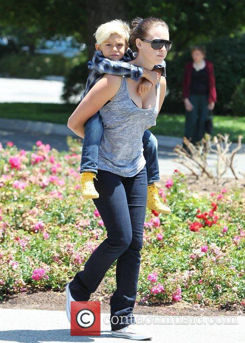 Kingston Rossdale gets a piggy-back ride from his...