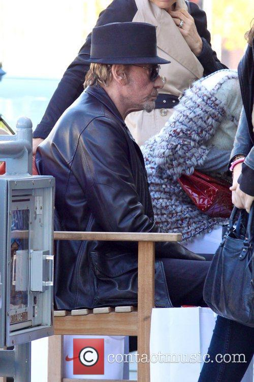 Johnny Hallyday sitting on a bench as he...