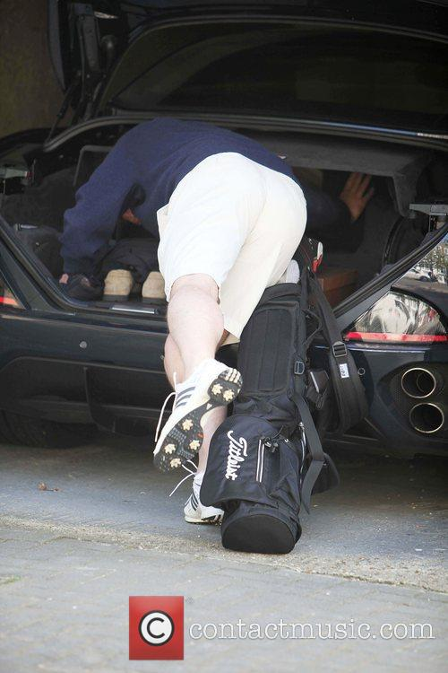 Hugh Grant unloads his golf clubs from the...