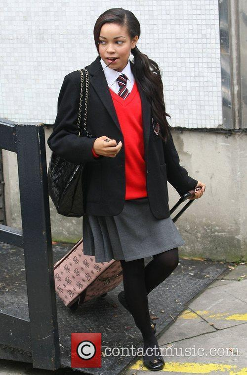Wearing her school uniform and pulling a suitcase