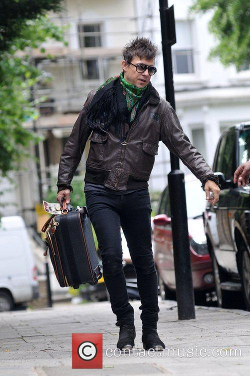 Leaving his house carrying a suitcase