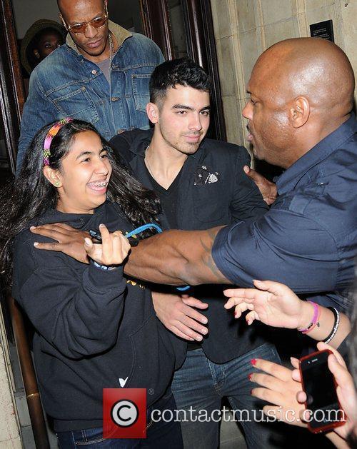 A fan is held back by Joe Jonas's...