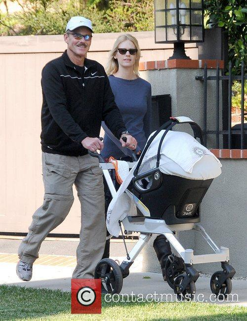 New mother January Jones walking with her father...