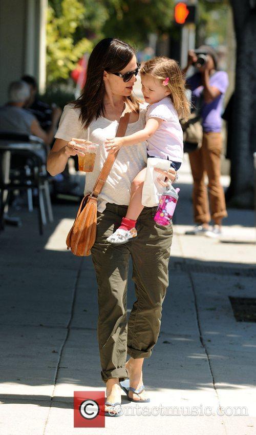 Jennifer Garner carries her daughter Seraphina Affleck while...