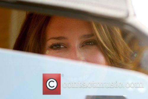 Jennifer Love Hewitt smiling as she looks through...